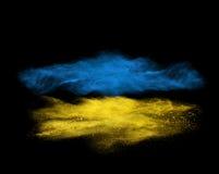 在黑色隔绝的蓝色和黄色粉末爆炸 免版税库存照片