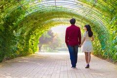 在绿色隧道的夫妇步行 库存图片