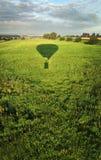 在绿色领域的气球阴影从天空  库存图片
