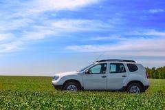 在绿色领域的白色SUV 免版税库存图片
