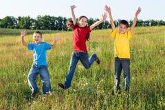 在绿色领域的跳跃的孩子 免版税库存图片