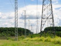 在绿色领域的高压电力杆反对与蓝天白色云彩 免版税库存照片