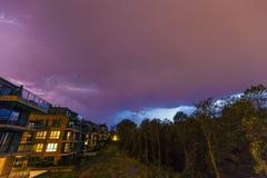 在紫色风雨如磐的天空的强的雷电在现代房子在晚上 免版税库存图片
