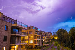 在紫色风雨如磐的天空的强的雷电在现代房子在晚上 免版税库存照片