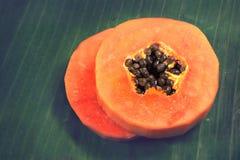 在绿色香蕉叶子的切片成熟番木瓜 免版税库存图片