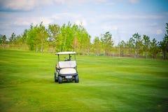 在绿色高尔夫球领域的白色高尔夫球汽车在美好的晴天 免版税库存图片