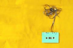 在黄色织品材料背景的盒式磁带 免版税库存照片