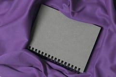 在紫色织品的笔记本,笔记本是灰色的,葡萄酒笔记本盖子 免版税库存照片