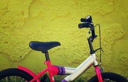 在黄色织地不很细墙壁旁边的孩子自行车 库存照片