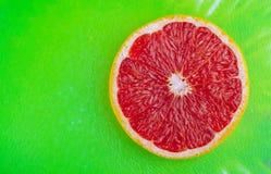 在绿色织地不很细背景的新鲜的充满活力的葡萄柚 免版税库存照片