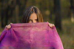 在紫色围巾后 免版税库存图片