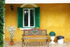 在黄色水泥墙壁上的绿色窗口 免版税图库摄影