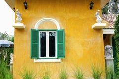 在黄色水泥墙壁上的绿色窗口 库存图片