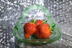 在绿色玻璃盘的草莓有bokeh背景 免版税库存图片