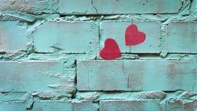 在绿色绘的破裂的砖墙上的两个心脏贴纸 库存图片