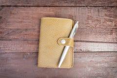 在黄色组织者顶部的笔有在木背景的皮革盖子的 图库摄影