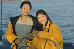 在黄色滑雪衫的夫妇在风船方向盘  免版税库存图片