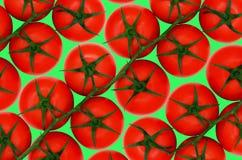 在绿色backround的红色蕃茄 免版税库存照片