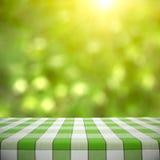 在绿色Bokeh的野餐桌 图库摄影