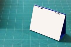 在绿色cuting的boad的白纸日历 免版税库存照片