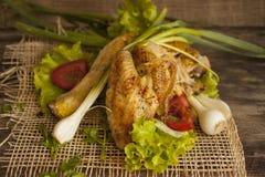 在莴苣叶子的油煎的母鸡在委员会的 免版税库存照片