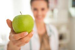 在给苹果的医生妇女的特写镜头 库存图片