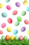 在绿草和飞行的复活节彩蛋在天空中 免版税库存照片