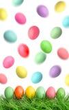在绿草和飞行的复活节彩蛋在天空中 库存照片