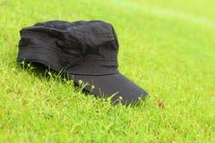 在绿草放置的盖帽 免版税库存图片