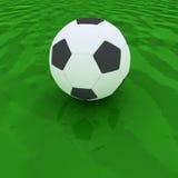 在绿草沥青的足球 免版税库存照片
