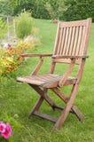 在绿草的一把木椅子 免版税库存图片