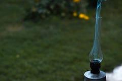 在绿草的一盏抽烟的老煤油灯 免版税库存图片