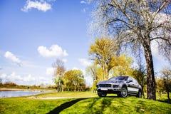 在绿草的一辆汽车在湖附近 免版税库存照片