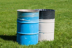 在绿草的两个垃圾桶 免版税库存图片