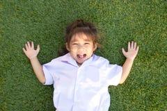 在绿草的亚洲泰国儿童微笑 库存图片