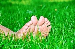 在绿草的女性脚 免版税库存照片