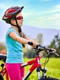 在绿草的妇女旅行的自行车在夏天公园 库存图片