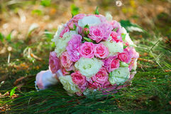 在绿草的婚姻的新娘花束 免版税库存图片