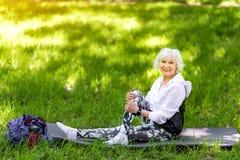 在绿草的快乐的年长夫人训练 免版税库存图片