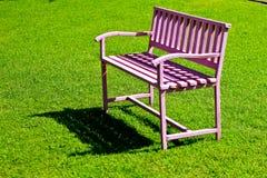 在绿草的桃红色钢长凳 免版税图库摄影