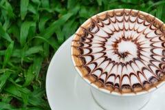在绿草的热的咖啡 免版税库存照片