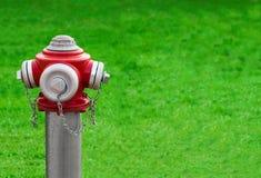 在绿草的现代红色消防栓 免版税库存照片