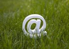 在绿草的电子邮件标志 免版税库存图片