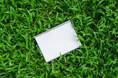 在绿草的白色笔记本 库存图片