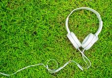 在绿草的白色耳机 有个人设备的夏天草坪 免版税库存照片