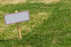 在绿草的空白的标志 免版税库存照片