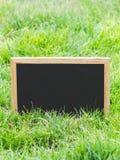 在绿草的空白的黑板 免版税库存照片