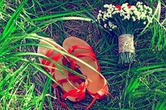 在绿草的红色凉鞋谎言 免版税库存照片