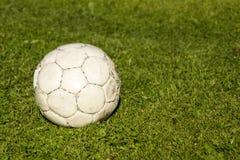 在绿草的老破旧的球 免版税库存图片