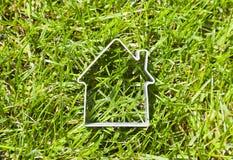 在绿草的议院形状 免版税库存图片